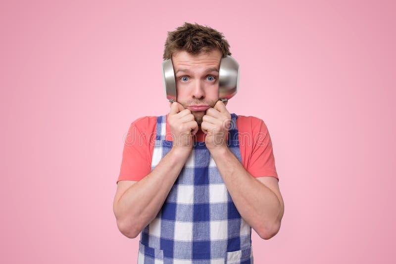Mann im Schutzblech, das seine Ohren mit Wannen bedeckt lizenzfreies stockbild