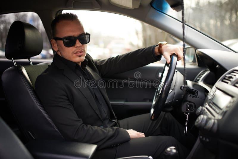 Mann im schwarzen Anzug, der hinter dem Rad sitzt stockfotografie