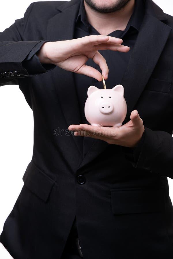 Mann im schwarzen Anzug setzt Münze in Sparschwein ein stockfotos