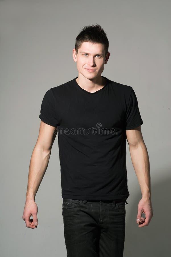 Mann im schwarzen Hemd auf grauem Hintergrund lizenzfreie stockfotos