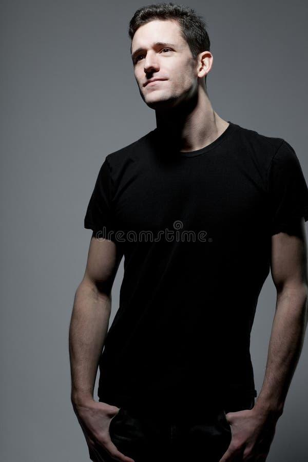 Mann im schwarzen T-Shirt, das auf grauem Hintergrund aufwirft. stockbild