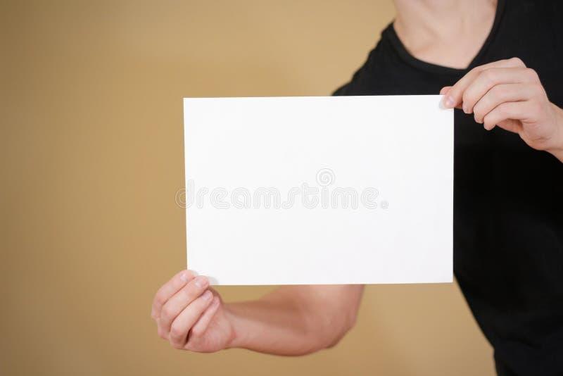 Mann im schwarzen T-Shirt, das leeres Papier des Weiß A4 hält Broschüre prese lizenzfreies stockbild