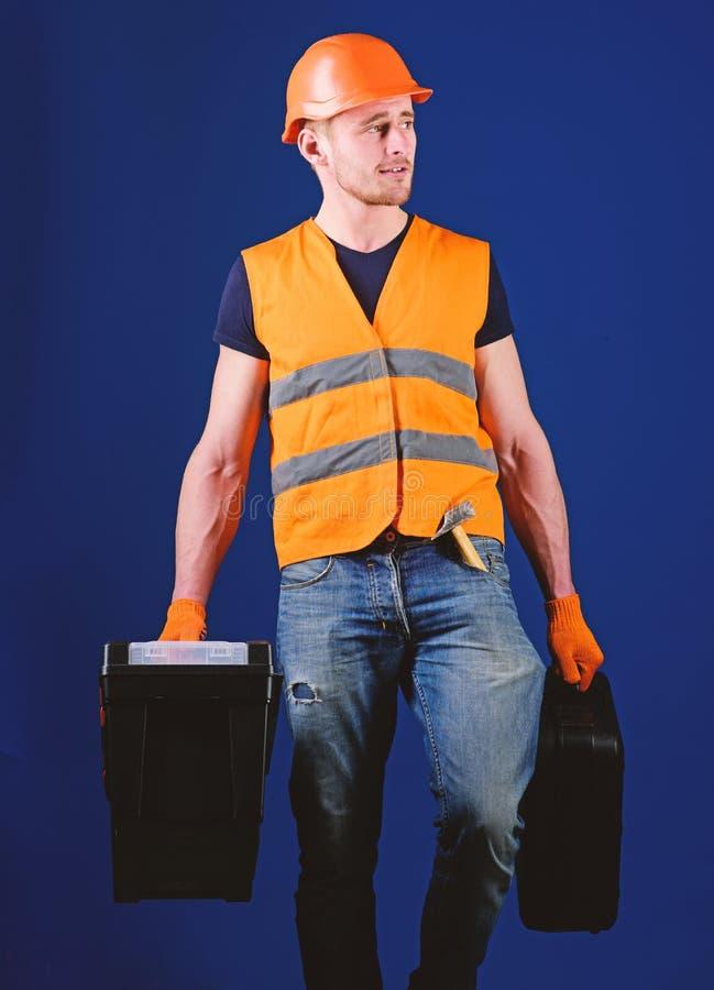 Mann im Sturzhelm, Schutzhelm hält Werkzeugkasten und Koffer mit Werkzeugen, blauen Hintergrund Berufsschlosserkonzept heimwerker lizenzfreie stockfotografie
