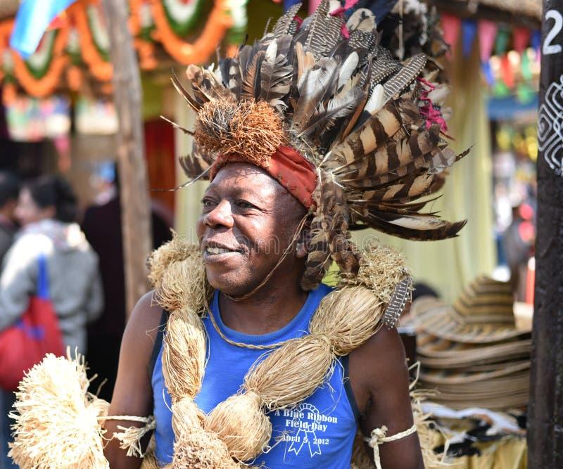 Mann im traditionellen afrikanischen Stammes- Kleid, die Messe genießend stockbild
