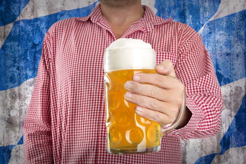 Mann im traditionellen bayerischen Hemd hält Becher Bier lizenzfreies stockfoto