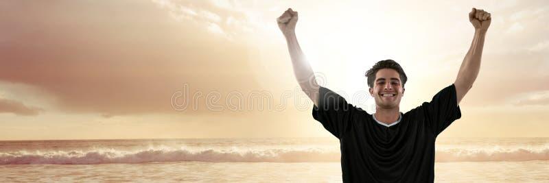 Mann im Trikot feiernd auf Sonnenuntergangstrand mit Aufflackern stockfotografie