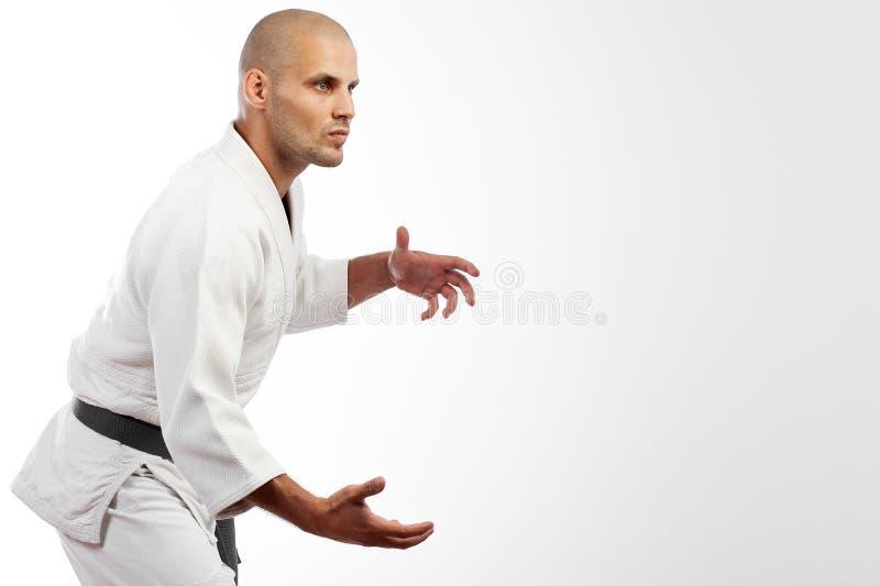 Mann im weißen Kimono, der auf weißem Hintergrund aufwirft stockfotografie