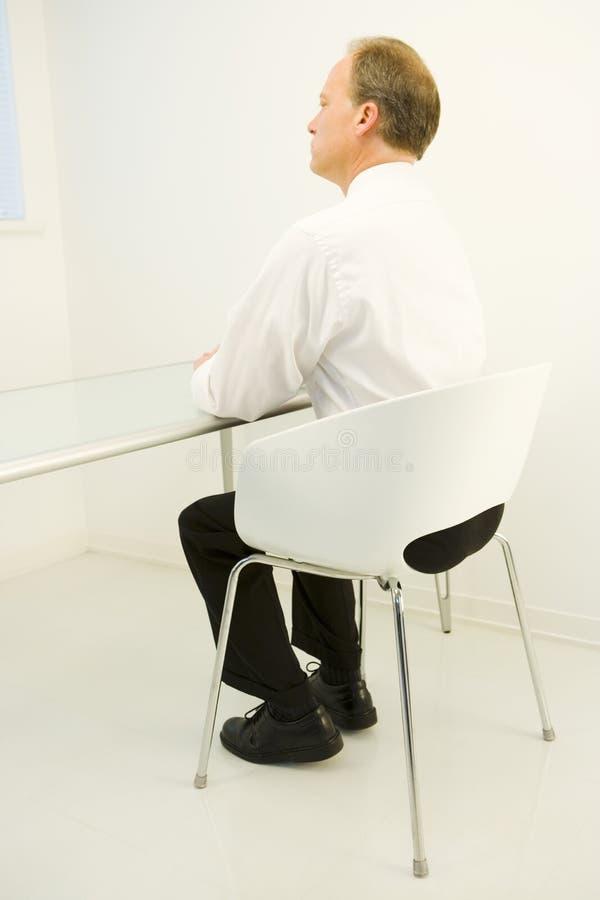 Mann im weißen Raum am Tisch   stockfoto