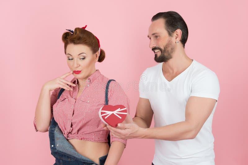 Mann im weißen T-Shirt gibt schönem Brunettepin-up-girl im Denim eine Geschenkbox mit Band in Form von rotem Herzen stockfotografie