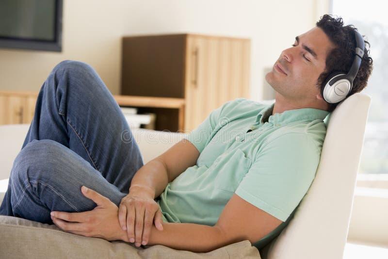 Mann im Wohnzimmer hörend zu den Kopfhörern lizenzfreie stockfotografie