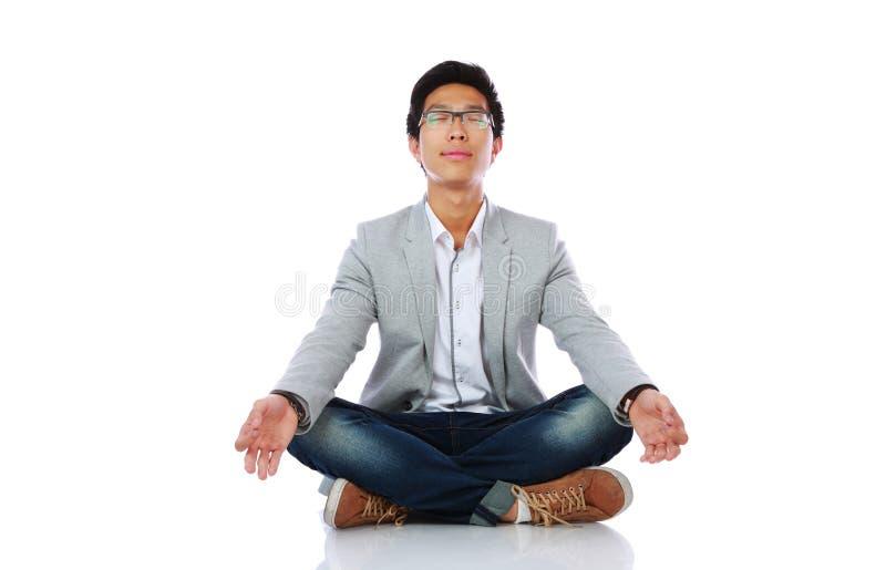 Mann im zufälligen Stoff meditierend stockbild