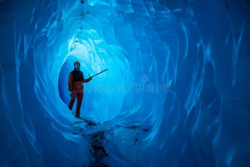 Mann innerhalb einer Eishöhle des schmelzenden Gletschers Schneiden Sie durch Wasser vom schmelzenden Gletscher, die Höhle läuft  lizenzfreies stockfoto