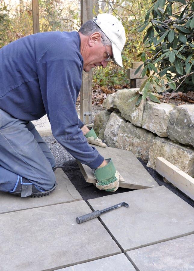 Mann installiert Steinplatte auf Patio stockfoto