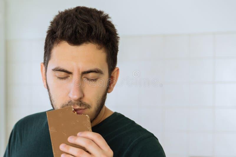 Mann isst Schokolade mit großem Vergnügen Begriffsfoto über Bonbons lizenzfreies stockfoto