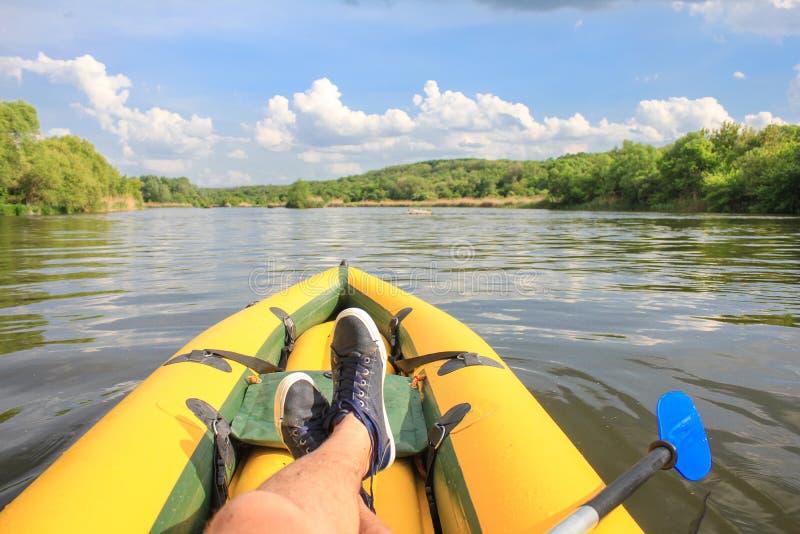 Mann ist Entspannung auf gelbem Boot der Fluss POV lizenzfreies stockbild