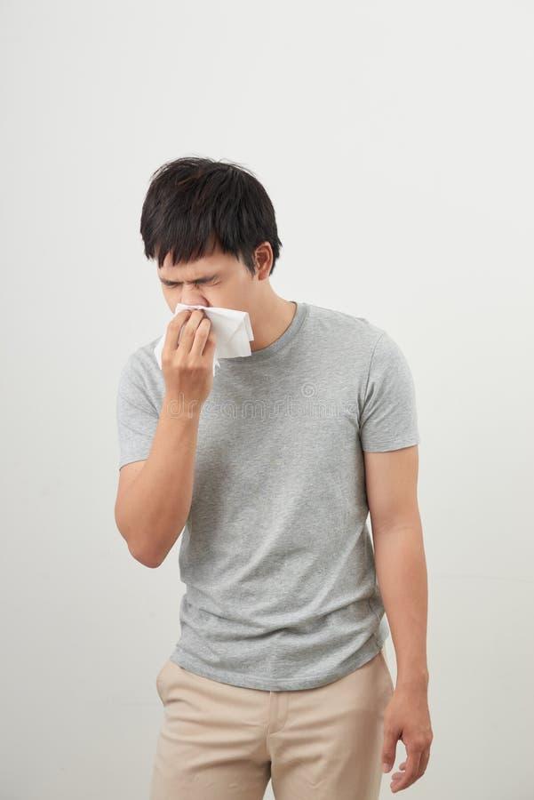 Mann ist krank niesend und mit dem weißen Hintergrund, asiatisch stockbild