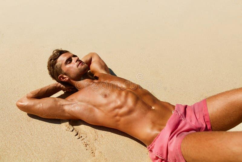 Mann-Körper auf Strand Sommer-männliches Lügen auf Sand am Erholungsort stockbild