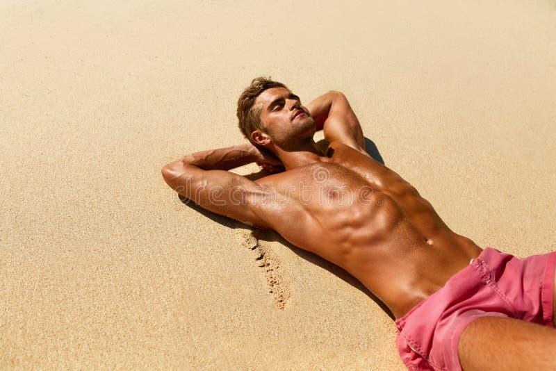 Mann-Körper auf Strand Sommer-männliches Lügen auf Sand am Erholungsort stockfoto