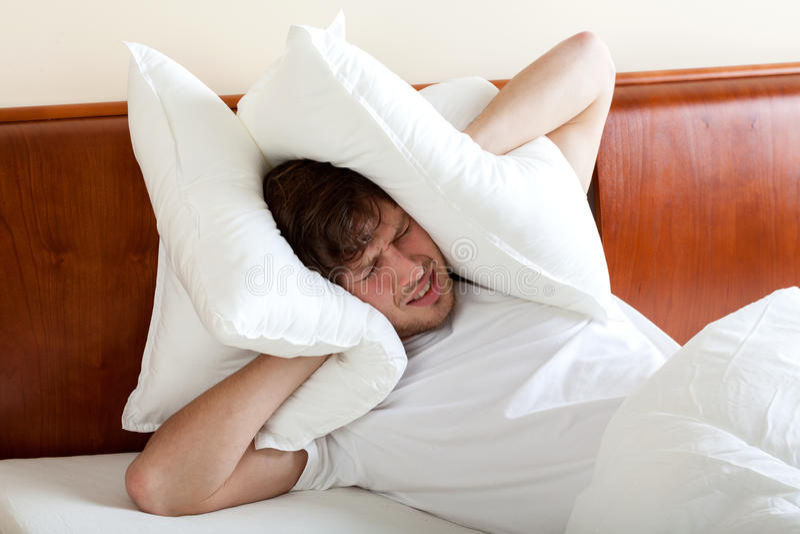 Mann kann nicht wegen der Geräusche schlafen lizenzfreie stockfotos