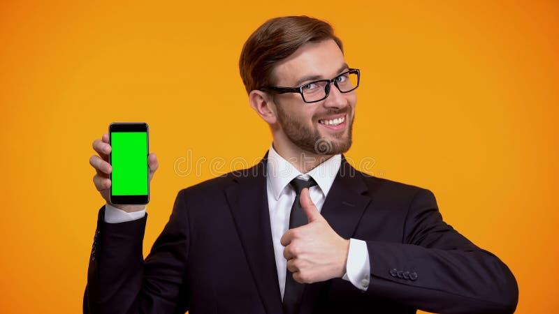 Mann in Klagenholding Smartphone mit dem gr?nen Schirm, Daumen herauf Gesch?ft App zeigend lizenzfreie stockfotos