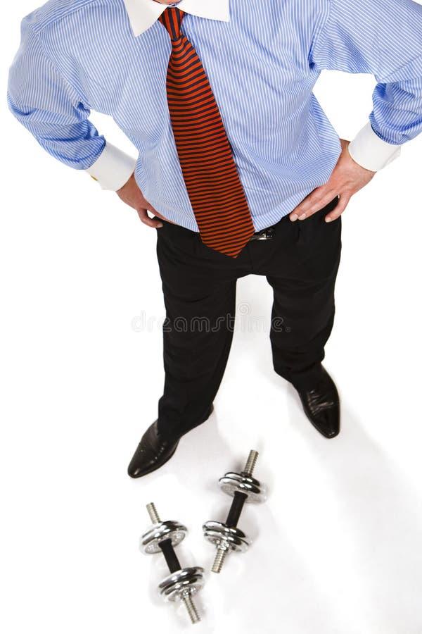 Mann kleidete den Anzug, der betriebsbereit ist, Dumbbells anzuheben lizenzfreies stockbild