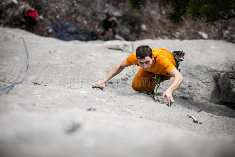 Mann klettert einen Felsen stockfotos