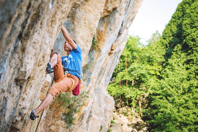 Mann klettert Felsen stockfotos