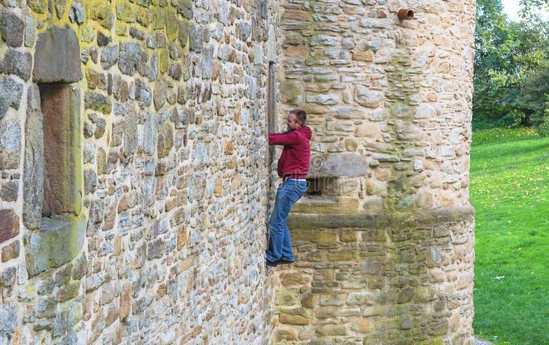 Mann klettert oben eine Schlosswand stockfotografie