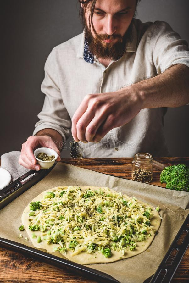 Mann kocht Pizza mit Brokkoli- und Pestosoße stockfotografie