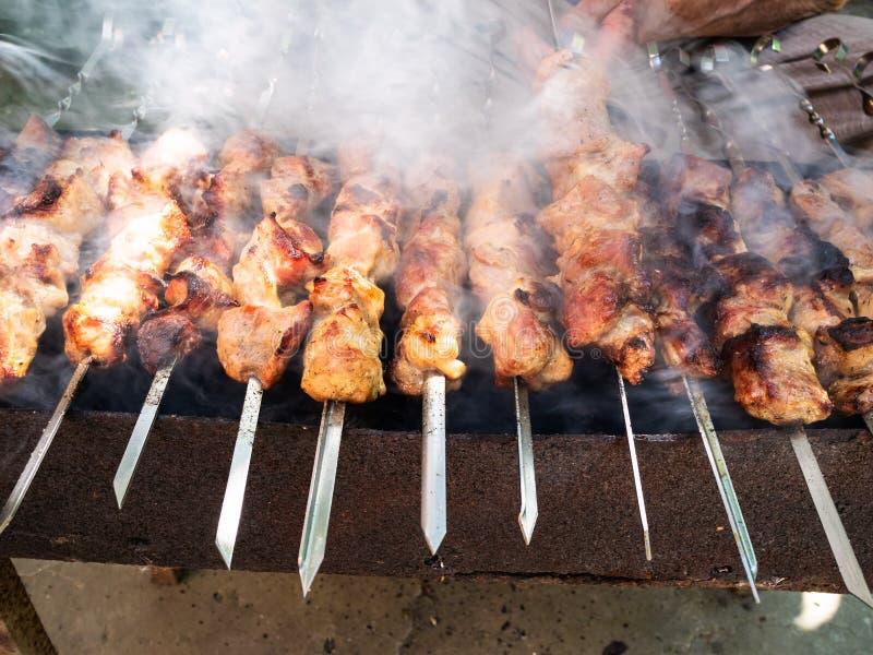 Mann kocht viele Kebabs auf Messingarbeiter im Freien lizenzfreie stockfotos