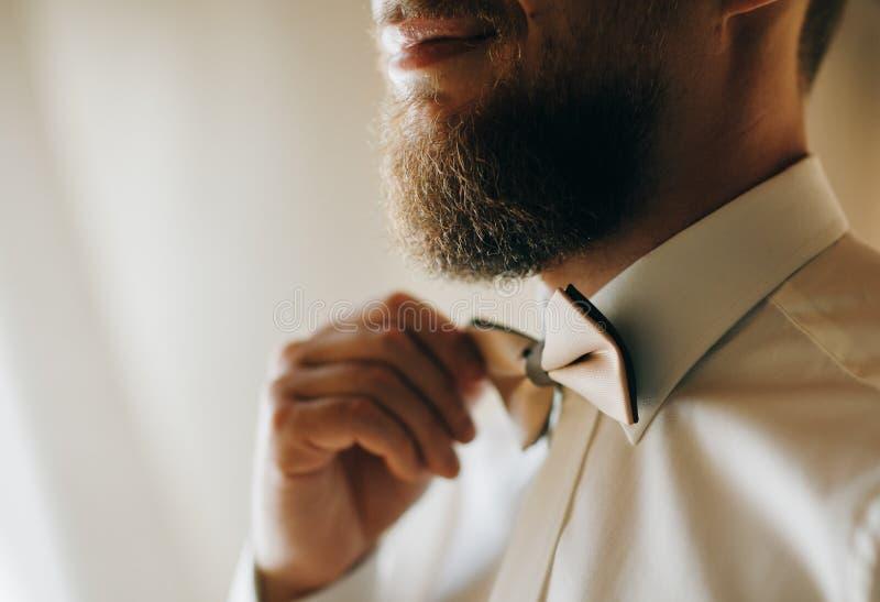 Mann korrigiert das des Schmetterlingsnahaufnahmetragende weiße Hemd des Kastens Mannes und justiert bowtie unter Verwendung der  stockbilder