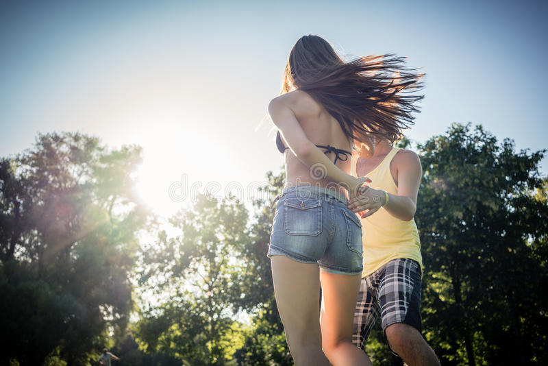Mann kręcenia kobiety taniec w trawie w lato parku obraz royalty free