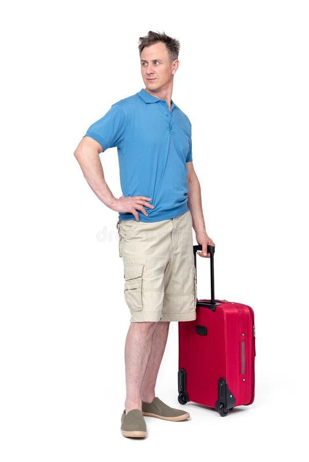 Mann kurz gesagt, blaue T-Shirt Stände mit einem roten Koffer, lokalisiert auf weißem Hintergrund Passagier mit Gep?ck stockbild