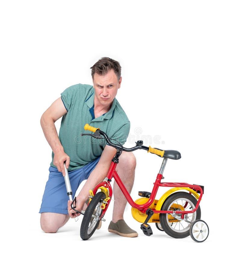 Mann kurz gesagt und ein T-Shirt pumpendes Rad am Fahrrad der Kinder Getrennt auf wei?em Hintergrund stockfoto