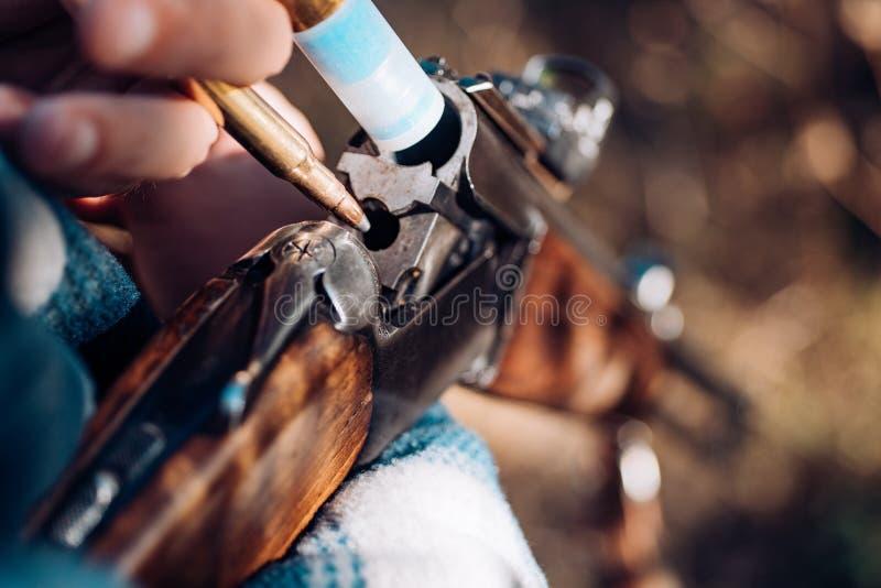 Mann lädt ein Jagdgewehr auf Amerikanische Jagdgewehre Jäger mit Schrotflintengewehr auf Jagd lizenzfreie stockfotos