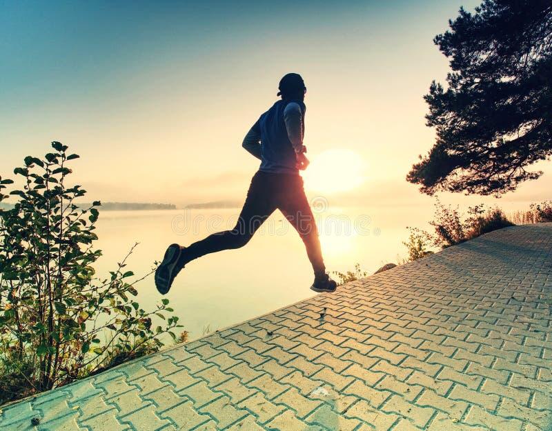 Mann läuft auf Pflasterung in der Seebucht Regelmäßiges Morgentraining stockbild