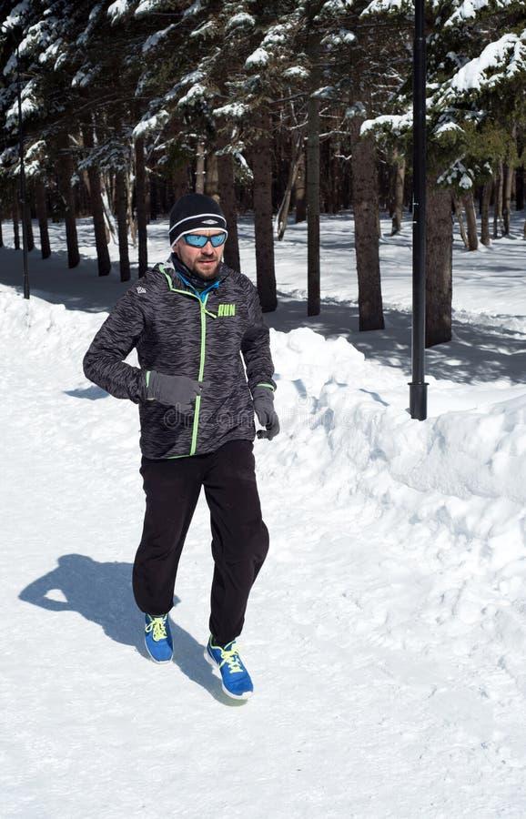 Mann-laufendes Rütteln im Winter Forest Snow lizenzfreie stockfotografie