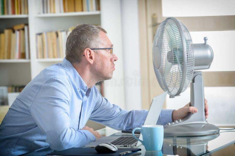 Mann leidet unter Hitze im Büro oder zu Hause lizenzfreie stockfotografie