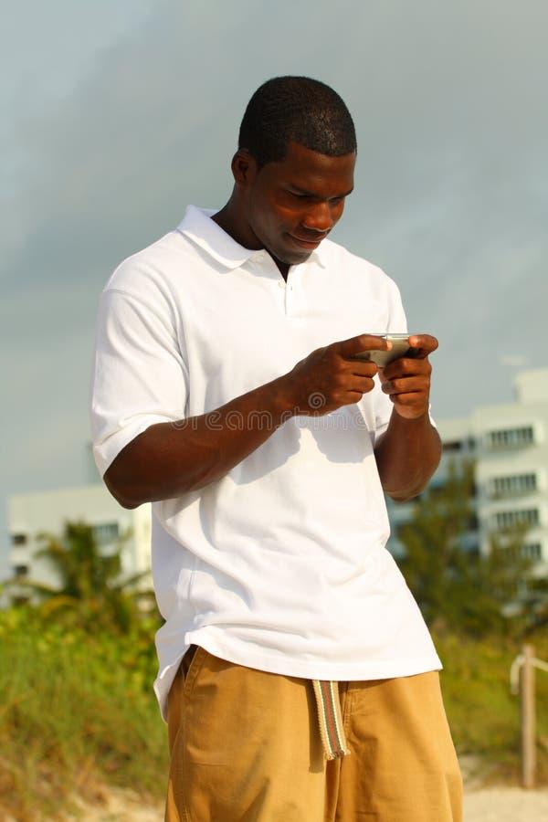 Mann-Lese-eMail auf dem Strand lizenzfreie stockfotos