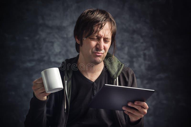 Mann-lesende schlechte Nachrichten auf Digital-Tablet-Computer lizenzfreies stockbild