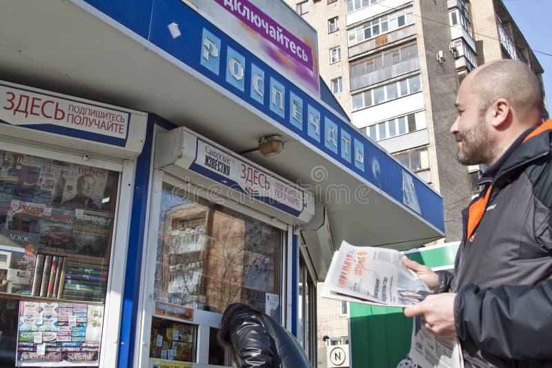 Mann liest die russische Zeitung stockbild