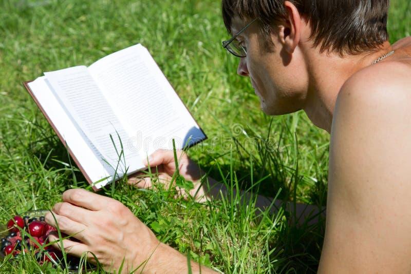 Mann liest ein Buch auf dem grünen Gras stockfoto