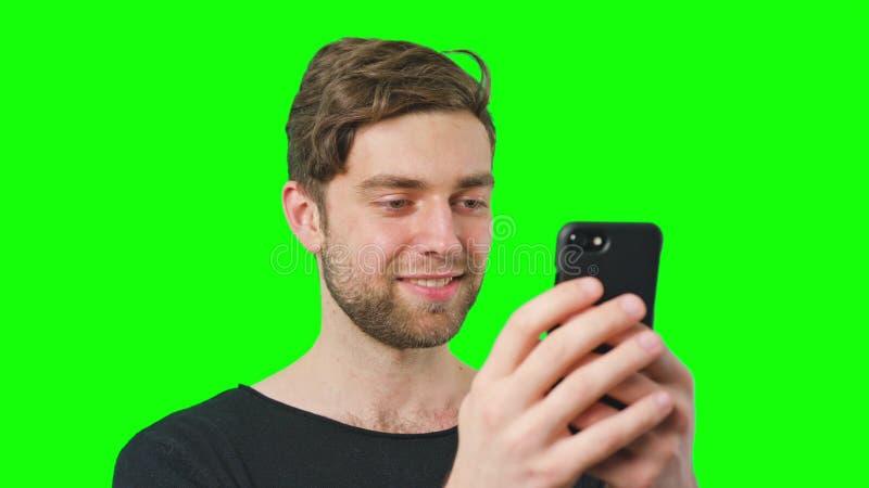 Mann liest Mitteilungen auf Telefon-Schirm stockbild