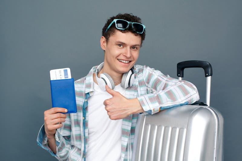Mann lokalisiert auf der grauen Wandtourismus-Konzeptstellung, die auf Kofferholdingpaß mit dem Kartendaumen herauf das Schauen s stockbild