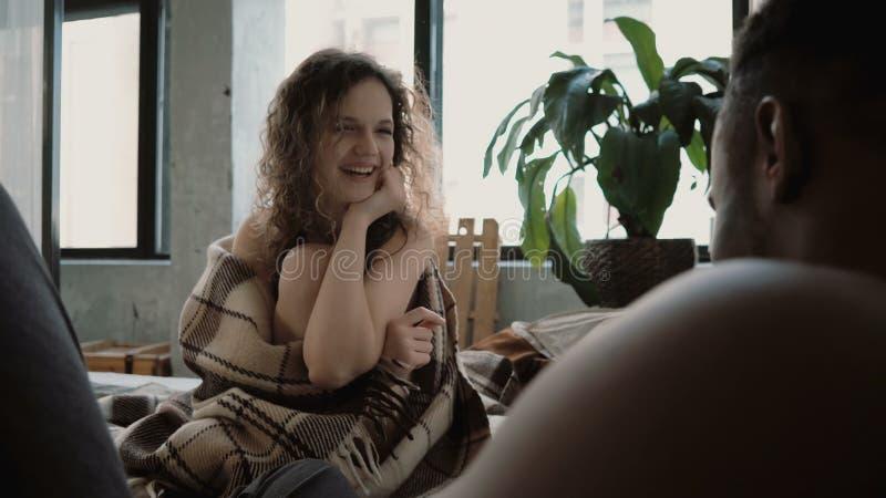 Mann macht Fotos auf Filmkamera der Frau Weibliches Lachen, wickelnd in der Decke ein Multiethnisches Paar schaut zusammen glückl lizenzfreies stockbild