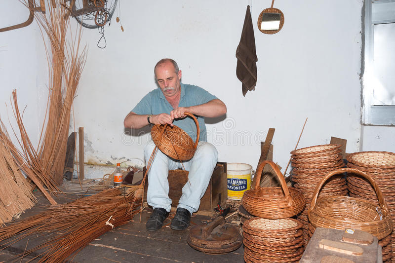 Mann macht Reedkörbe in einer Einfassungsfabrik bei Madeira, stockbilder