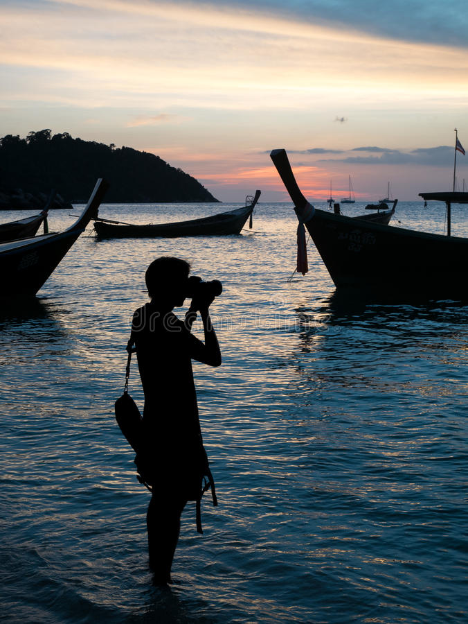 Mann machte ein Foto von Booten und von Sonnenuntergang am Strand lizenzfreies stockfoto
