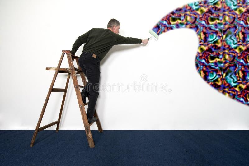 Mann-malende weiße Wand mit wilden Farben lizenzfreie stockfotos