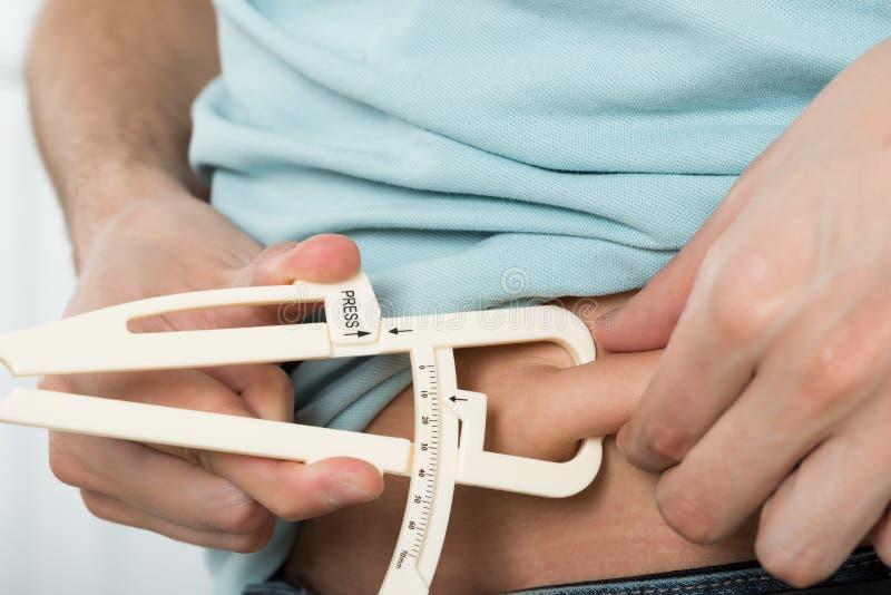 Mann-messendes Magen-Fett lizenzfreies stockbild