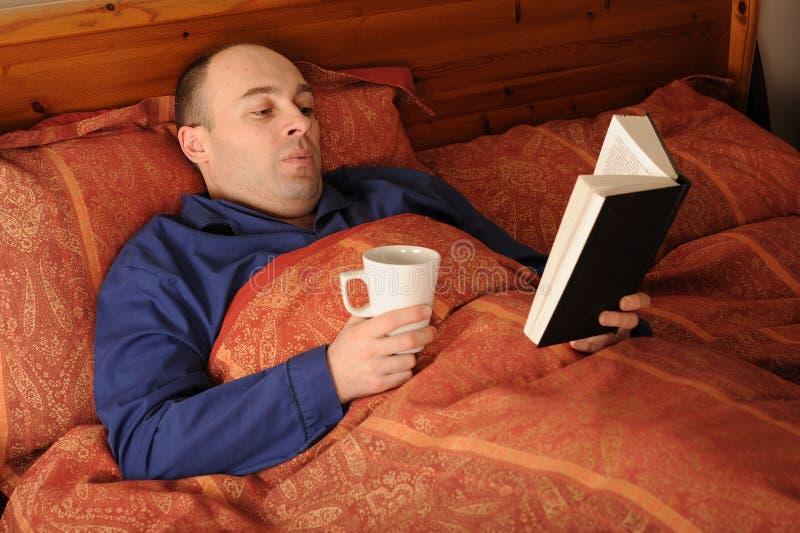 Mann-Messwert im Bett lizenzfreies stockbild